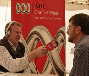 ABC radio journalist Bruce Reynolds (left) points a microphone towards CSIRO ATNF Deputy Director Dr Lewis Ball (right). There is an ABC Central West banner in the background.