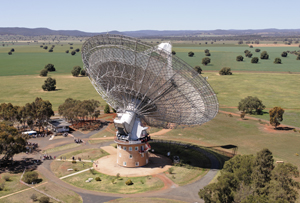 An aerial view of the Parkes radio telescope. The big dish is pointing away from and to the right. Several groups of people can be seen in the grounds around the telescope. In the distance is a mountain range.