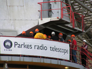 A group of people in orange hardhats are on the azimuth track of the Parkes telescope behind a banner with the CSIRO logo and 'Parkes radio telescope' on it