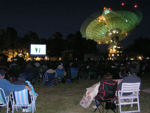 In the foreground many people on blankets and picnic chairs watch the movie with the telescope in the background
