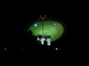 Two men appear on the dish surface on the movie screen with the telescope in the background