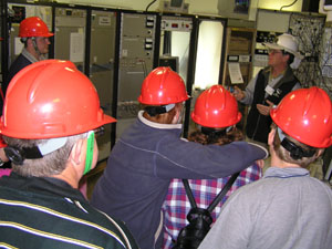 Brett in a white hard hat (back right) is facing a group of people in red hard hats (their backs to camera). There is various electronic equipment in the background.