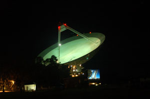 The Parkes radio telescope lit up at night with a movie screen in the front showing the dish in the movie the dish pointing in a similar direction
