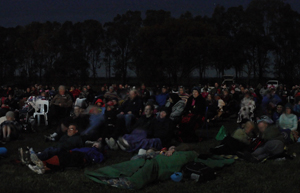 A crowd of people at night are sitting on blankets and picnic chairs. They are all looking off left where the movie is screening