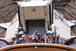 A group of people with green hard hats walk around the azimuth track of the Parkes telescope below the counterweight
