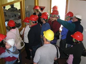 A group of people in red and yellow hard hats look through a large window (left) into a room of computers. Lewis in a white hard hat (back right)  is behind the group explaining the computers.