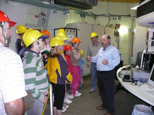 John Sarkissian at the right is facing a large group of people (left) in yellow hard hats who are listening to him. There is various electronic equipment behind them.