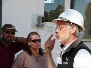Dr Dave McConnell in a white hard hat points to his eye. There are two people in the background who are part of the larger group (off left of frame)
