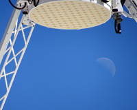 A close up of a radio receiver with the moon in the background.
