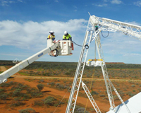 Two men in an elevated work platform working on a receiver at the top of a dish-like antennas in an Australian outback setting. Credit: CSIRO