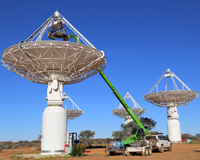 Daytime photo of dish-like radio antennas in an outback setting. Credit: CSIRO