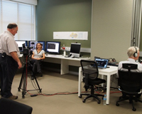 ASKAP team member speaks to a camera in front of a row of computer screens in the Science Operations Centre. Credit: CSIRO.