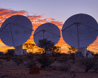 Three ASKAP antennas at the Murchison Radio-astronomy Observatory against a sunrise backdrop.