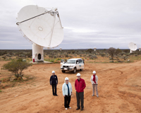Four people looking toward the camera in front of several dish-like antennas in an Australian outback setting. Credit: SKA Australia